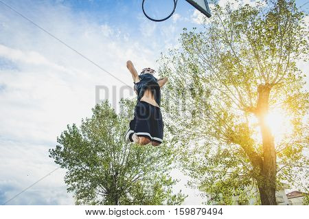 Basketball athlete doing huge slam dunk on the court in urban grunge camp with back light - Young man in action outdoor at sunset - Sport concept - Warm raw filter with focus on man