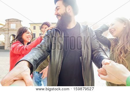 Young friends having fun in city old town center with back light - Group of cheerful happy people smiling and playing outdoor - Friendship and youth concept - Warm filter - Focus on bearded man