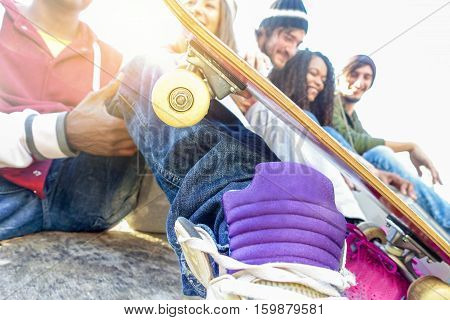 Group of happy friends having fun outdoor in urban city park with sun back light - Young youth people socializing - Leisure and friendship concept - Focus on skateboard wheel - Warm filter