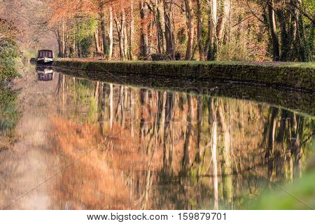 Narrow boat on Kennet and Avon Canal in autumn. Autumnal scene with orange leaves of beech trees reflected in still water of canal in English countryside