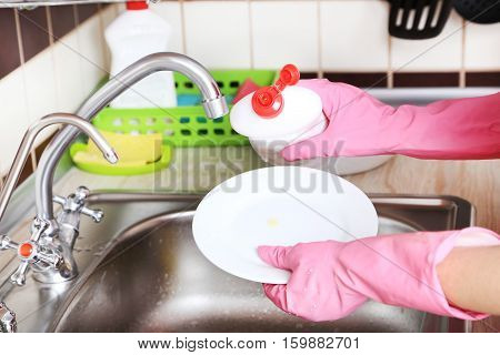 Female hands in gloves washing dish, close up