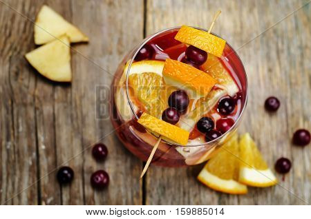 Apple cranberry orange sangria on wood background