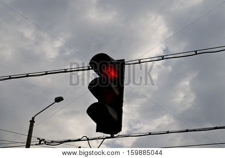 Traffic light with red light against the morning sky