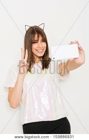Cool beautiful young millennial Caucasian brunette woman in sequined light pink shirt and cat ears taking a selfie on smart phone. Happy young teenage girl posing photographing herself on cellphone.