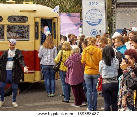 MOSCOW, RUSSIA - August 13, 2016: Townspeople stand in a queue for to see the inside of the retro bus interior. Festive occasion of the Moscow bus on the Frunze Embankment. August 13, 2016 in Moscow, Russia