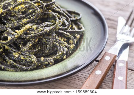 Portion of black pasta with pesto sauce on the wooden table