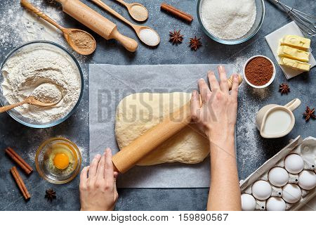 Dough bread, pizza or pie recipe preparation. Female baker hands rolling dough with pin. Food ingridients flat lay on kitchen table. Working with butter, yeast, flour, eggs, pastry or bakery cooking.