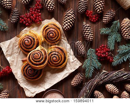 Sweet Homemade christmas baking. Cinnamon rolls buns with cocoa filling. Kanelbulle swedish dessert. Top view. Festive decoration with pine cones and Christmas tree