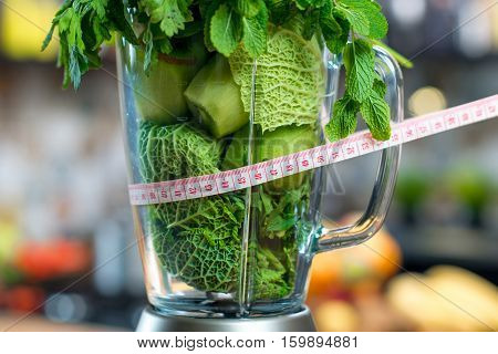 Close up view on the blender full of green fruits and vegetables ready to mix with meter in the kitchen. Healthy vegetarian diet for weight loss and detox