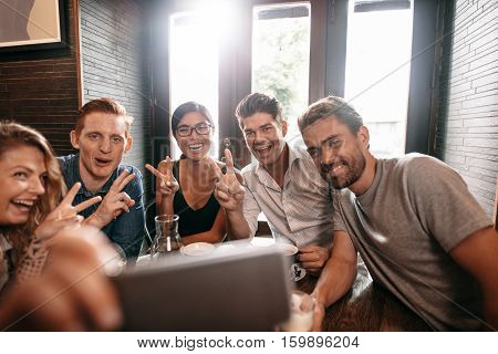 Multiracial people having fun at cafe taking a selfie with mobile phone. Group of young friends sitting at restaurant taking self portrait with smart phone with victory sign.