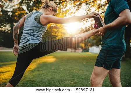 Male coach helping young woman exercising in park. Trainer helping woman in leg stretching workout.