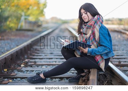 Young girl reading alone in the railroad