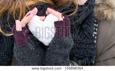 Woman Hands Holding Heart Shaped Snowball