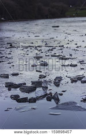 Frozen bits of ice over pond in St Albans city in winter. Shallow depth of field.