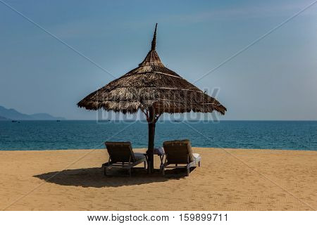 A view of Nha Trang bay in Vietnam on a sunny day with two sun lounger's under a palm umbrella.