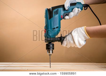 Closeup of female hands in gloves drilling wooden plank. Green drill against neutral orange copy space
