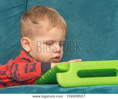 Small child intently playing with a computer tablet.