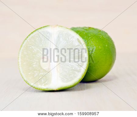 Lemon Or Lime Fruit With Half Cross Section And Partial Section Isolated On Wooden Board