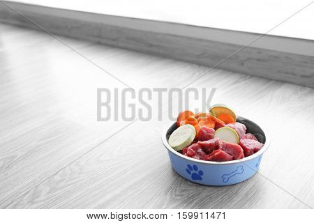 Organic dog food in a bowl on a wooden floor