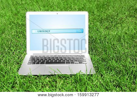 Modern laptop on green grass. Word UROLOGY at search engine. Health care concept.