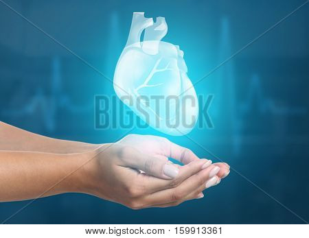 Female hands with heart on blue background. Cardiology concept.