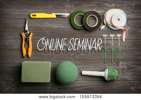 Text ONLINE SEMINAR with florist equipment on wooden background. Florist and floral design tutorial concept.