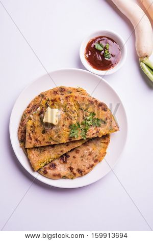 Daikon, radish, mooli or muli paratha or stuffed radish paratha, indian or pakistani favourite recipe served with butter and tomato ketchup, selective focus