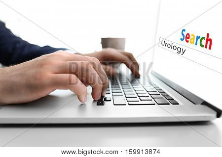 Man searching information on internet, closeup. Word UROLOGY at search engine. Health care concept.