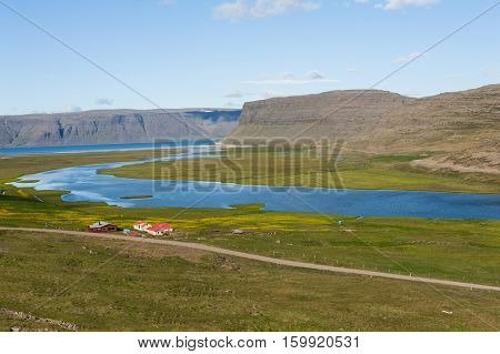 Mighty fjords rise from the sea and a farm.  Westfjords Peninsula, northwestern Iceland