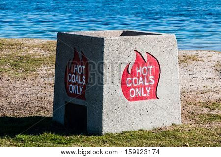 Container for disposal of hot coals on beach.