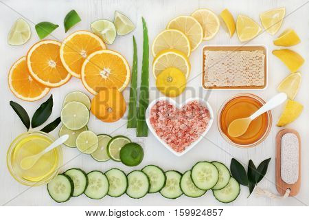 Natural skincare products and ingredients with citrus fruit, aloe vera and cucumber with almond oil, himalayan salt, honey and pumice on distressed wood background.