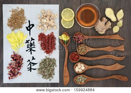 Chinese herbal tea collection with calligraphy on rice paper with tea cup and herbs in wooden spoons, teas also used in alternative medicine. Translation reads as chinese herb tea.