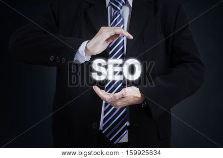 Close up of businessman hand holding SEO word while wearing formal suit. Concept of Search Engine Optimization