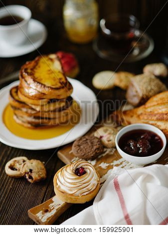 Breakfast table with french toasts, strawberry confiture and biscuits