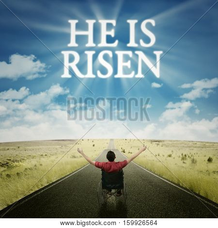 Image of disabled man sitting on a wheelchair and raising hands at the road while looking at text of he is risen in the sky