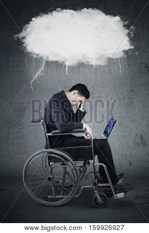 Portrait of stressful businessman sitting on wheelchair while using laptop with a thundercloud above his head