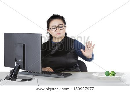 Portrait of fat woman refuse broccoli while sitting on the chair isolated on white background