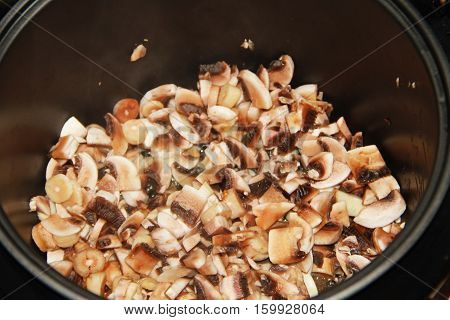 Sliced mushrooms cooking in a slow cooker