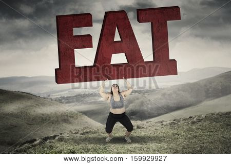 Picture of obese woman lifting a big fat word while standing in hills