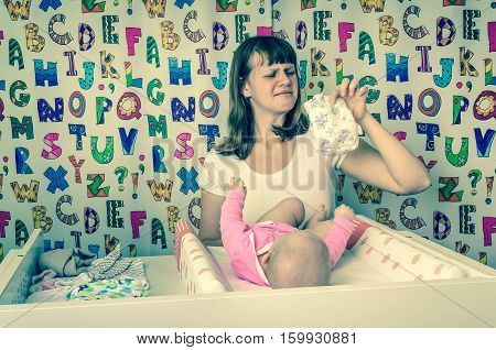 Mother Changing Smelly Diaper To Her Little Baby Girl