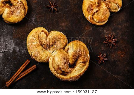 Cinnamon rolls in the form of heart on a dark metallic rusty background with cinnamon sticks and anise stars. Selective focus