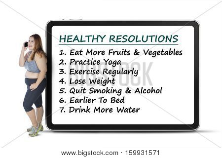 Obese woman standing with billboard with healthy resolutions text isolated on white background