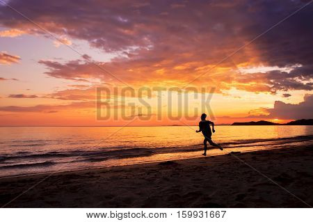 Silhouette of happy man running on the beach at sunset