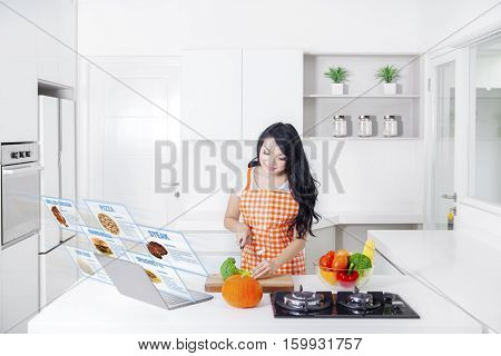 Portrait of attractive young woman is chopping broccoli and preparing food with a virtual food recipe on the laptop
