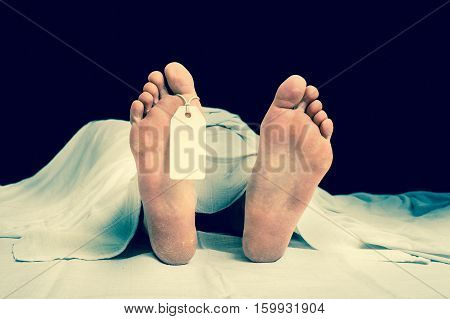 The dead man's body with blank tag on feet under white cloth in a morgue