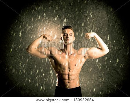 A handsome young body builder weightlifting while showing his muscular upper body in the rain concept