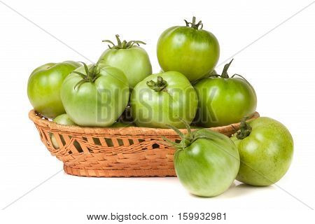 unripe green tomatoes in a wicker basket isolated on white background.