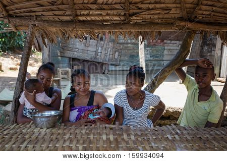 Malagasy Woman With Baby Resting Under Shelter