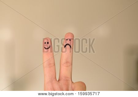Two Hand Drawn Emoticon Faces On A Persons Fingers