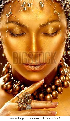 Gold Woman skin. Beauty fashion model girl with Golden make up, hair and jewellery on black background. Gold ring and necklace. Metallic, glance Fashion art portrait, Hairstyle and make up.